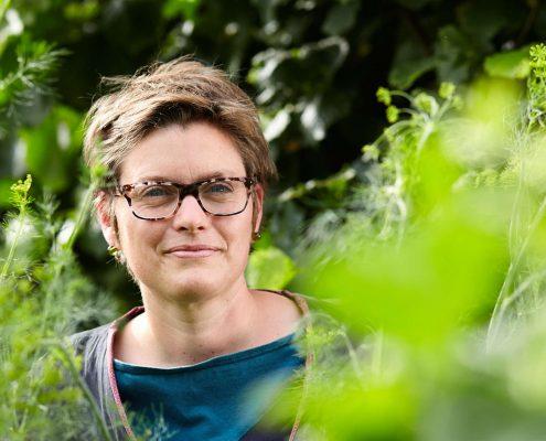 Kurzhaarige Frau mit schwarzer Brille steht in dichten grünen Pflanzen