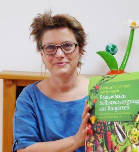 Kurzhaarige Frau mit schwarzer Brille hält Buch zu Selbstversorgung in die Höhe