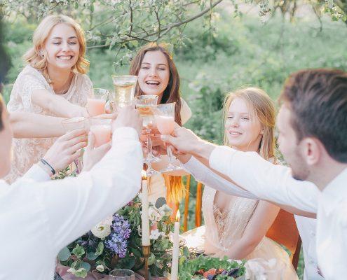 Junge Menschen an einem Tisch stoßen mit Getränken an