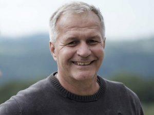 Freundlich lächelnder Mann mit grauen kurzen Haaren