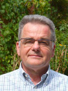 Portrait eines Mannes mit kurzen grauen Haaren und Brille