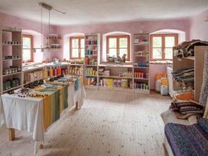 Blick in einen Raum mit diversen Produkten wie Teppichen, Lebensmitteln und Waschmitteln