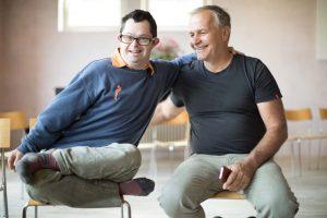 Ein Mann mit Down Syndrom sitzt neben Mann mit grauem Haar, beide lächeln fröhlich
