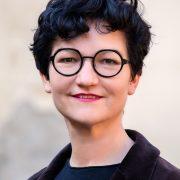 Portrait einer Frau mit kurzem schwarzen Haar und runder Brille