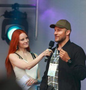 Rothaarige hübsche Frau hält Mikrofon und interviewt gutaussehenden sportlichen Mann