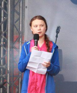 Junges Mädchen in rosa Bluse und blauer Jacke auf Bühne