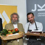 Vier Männer stehen vor JKU und Mensa Schildern und halten Gemüse