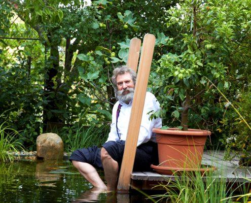 Mann mit grauem Rauschebart und Brill sitzt an Teich mit Füßen im Wasser