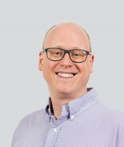 Mann mit Brille und Glatze lächelt freundlich