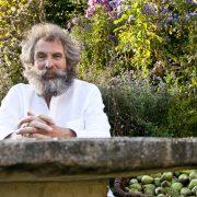 Bärtiger Mann an einem Steintisch vor wuchernden grünen Pflanzen