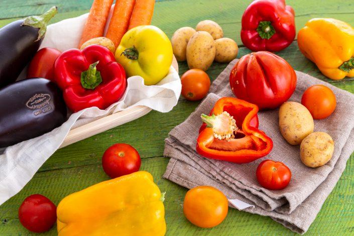 Buntes Gemüse auf grünem Tisch, Melanzani, Karotte, Erdäpfel etc.