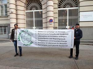 Zwei Männer halten ein Schild in die Höhe, wo Forderungen zu klimafreundlicher Architektur drauf stehen
