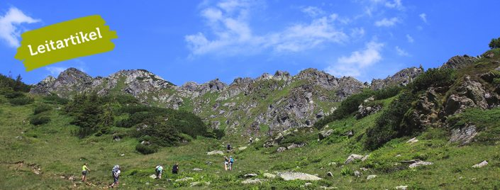 Mehrere Menschen besteigen einen Berg