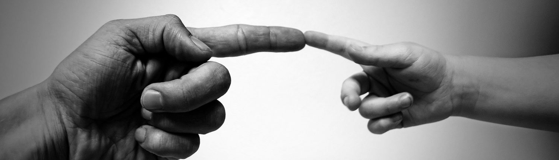 zwei Hände, wo sich nur die Zeigefinger berühren
