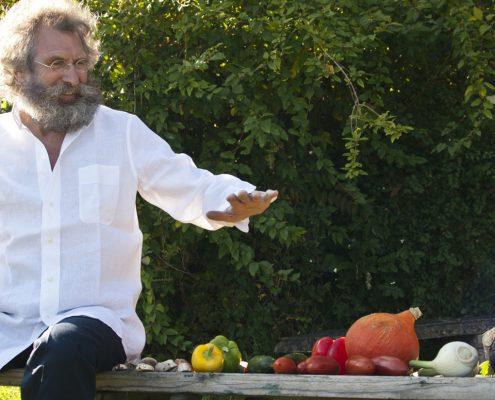Mann mit Rauschebart hält Hand über Gemüse, als würde er es beschwören wollen