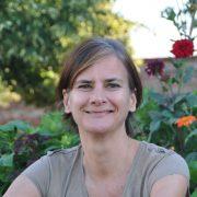 Portrait einer Frau mit kurzen gefärbten Haaren im Garten