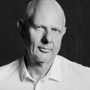 Portraitfoto in schwarz weiß eines glatzköpfigen Mannes in weißem Hemd