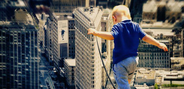 Kleinkinde balanciert über hohes Drahtseil zwischen Hochhäusern