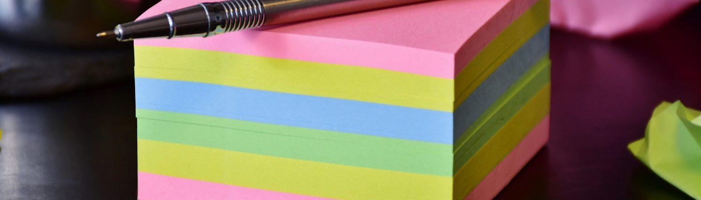 ein Block von bunten Zetteln mit einem Stift darauf