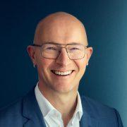 Mann mit Brille und Ohrringen lächelt