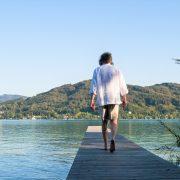 Mann in kurzer Hose und weißem Hemd geht auf einem Steg Richtung See
