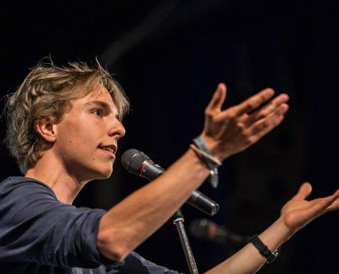 Junger Mann auf der Bühne gestikulierend